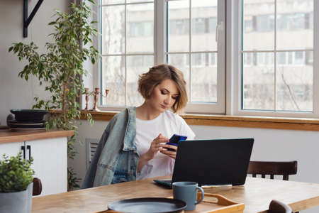 Remote Working From Home. Girl Freelancer Workplace In Kitchen With Laptop, Mug of Tea or Coffee. Concept Distance Learning, Self Isolation, Female Small Business, Shopping Online. Lifestyle moment. 免版税图像