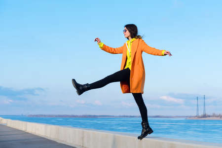 Lifestyle full length portrait of charming Millennial Hipster Girl in sunglasses, orange coat, yellow hoodie and black jeans against the background sea. Step Forward 免版税图像