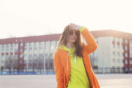 Young woman in lilac glasses, orange coat, yellow hoodie dances and plays with her hair. Trendy colorful casual outfit. Street Style.
