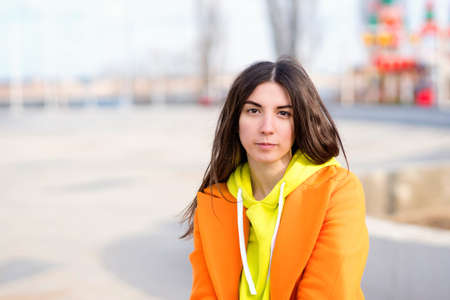 Millennial Hipster Girl in orange coat, yellow hoodie posing at urban background. Lifestyle portrait of stylish focused young woman. Real people concept