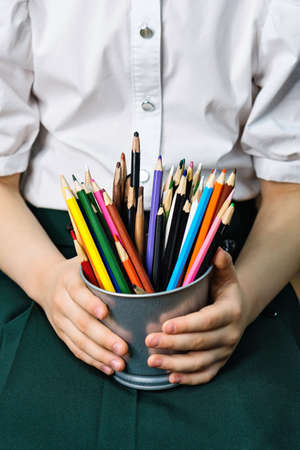 Collection of colored pencils. Close up. Drawing School Background. Unrecognizable Schoolgirl. Elementary school student in white blouse and green skirt holds bucket of colored pencils. 免版税图像