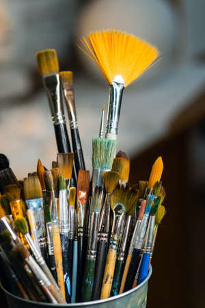 Set Collection Art Paint Brushes In Cup On Artists Desktop. Artistic Equipment In Studio