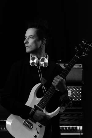 Black and white photo hipster guitar player with electric guitar and headphones in recording studio. Rock music concept. Portrait of confident heavy metal musician