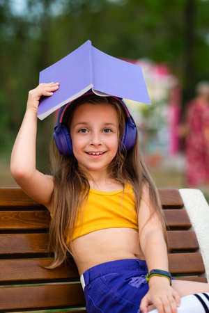 Portrait cute charming little girl listening podcast playlist modern track. Positive young lady in wireless headphones and casual clothes hold book and smiles. Soft focus 免版税图像