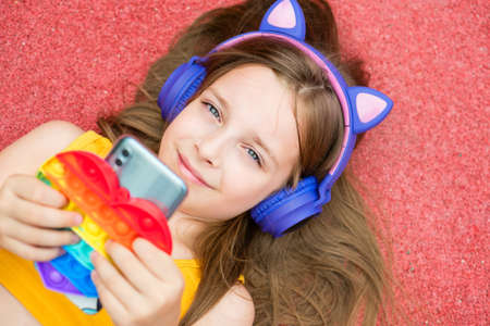 Pretty School girl hold smartphone and Anti-stress colorful toy pop . Young girl chatting friends, listen audio in a music app, modern technology earphones.