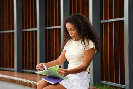 Mixed race black girl college student with books and notebooks outdoor campus. Image cheerful african american young woman. Comfort Zone. Non-digital world. Dark skinned lady studying 免版税图像
