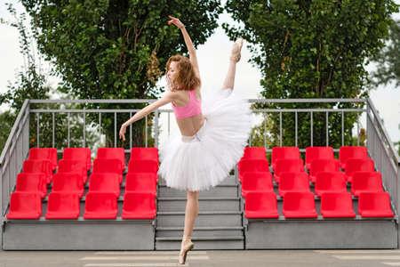 Ballerina practicing ballet dancing on street. Classic elegant girl ballet dancer moving outdoors. Young ballerina in white tutu. Ballet feet on point. Exercise.