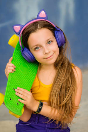 Portrait young hipster little girl with Skateboard and trendy wireless headphones on outdoor. Cute primary school student posing with longboard