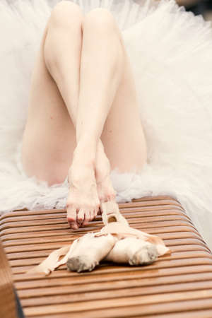 Ballerina feet without pointes outdoors. Cropped closeup perfect feminine long legs unrecognizable ballet dancer. Selective focus