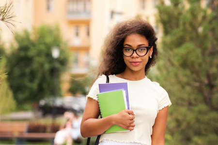 Mixed race girl in stylish glasses hold books outdoor campus. Portrait cheerful african american young woman. Dark skinned brunette lady with loose wavy curls african american hair. College student 免版税图像