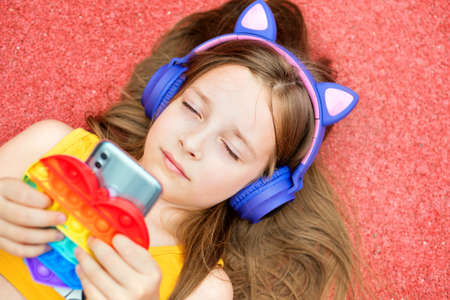 Schoolgirl hold smartphone and Anti-stress colorful toy pop it. Young girl closed eyes listens song in headphones