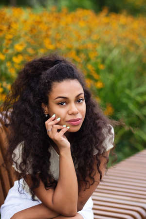 Dark skinned brunette Female with loose wavy curls african american hair. Outdoor Lifestyle Portrait of African American Young Woman. Hipster Mixed Race Black Girl. Soft focus. 免版税图像