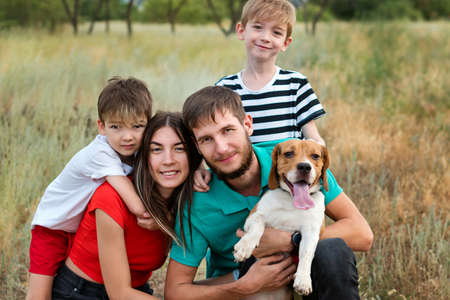 Family of Four Having Fun Playing with Purebred Beagle Dog In Rural Settings. Authentic group people portrait. Animals and friendship. Life in the Countryside