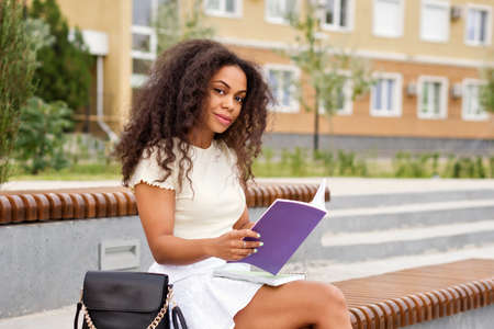 African american young woman. Mixed race girl with books and notebooks outdoor campus. Comfort Zone. Non-digital world. Dark skinned female with loose wavy curls african american hair college student