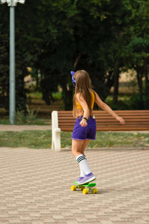 Young hipster little girl in fashionable sportswear with fashionable wireless headphones outdoors. Stylish elementary school student learning to skate in city park. Back view. Soft focus 免版税图像