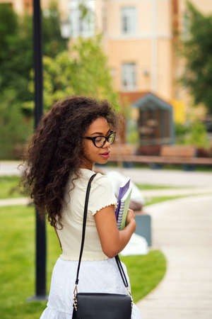 Mixed race girl in stylish glasses hold books outdoor campus. Portrait cheerful african american young woman. Minimal fashion style. Soft focus. Dark skinned female with loose wavy curlsblack hair