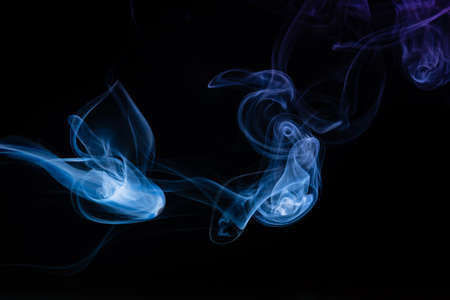 Abstract colored smoke moves on dark background. E-cigarette. Texture. Design elements. Wallpaper. Personal vaporizers fragrant steam. Concept of alternative non-nicotine smoking.