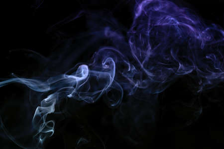 Abstract colored smoke moves on dark background. Wallpaper. Personal vaporizers fragrant steam. Concept of alternative non-nicotine smoking. E-cigarette. Texture. Design elements. 免版税图像