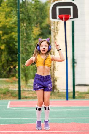 Cute girl in wireless headphones listening to music wearing fashionable sportswear jumping on sports ground. Rehearsal cheerleading performance