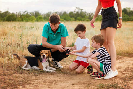 Group people. Mom, dad with two sons and pet. Young family walk and training dog in rural settings in summer day. Animal training concept.