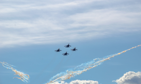 intimately: Flight groups of four fighter jets at an air show on a blue sky background, clouds, and thermal rocket plumes.