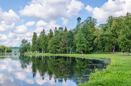 Oever van een prachtig meer met een weide en groene bosachtergrond en blauwe hemel met wolken in het Gatchina-Park in de buurt van St. Petersburg.