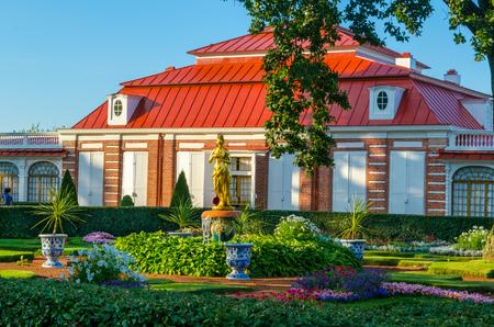 18 世紀、緑の木々、低木、青空と花に囲まれた赤い屋根のペテルゴフに建てられた宮殿博物館 Monplaisir。