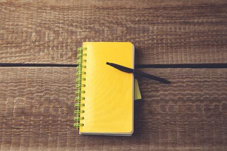 pen on notepad on wooden desk
