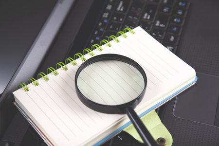 magnifier on notepad on  black notebook keyboard Imagens