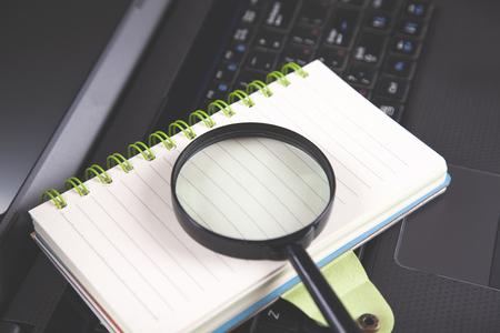 magnifier on notepad on  black notebook keyboard Reklamní fotografie