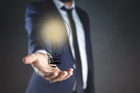young man hand light bulb in screen