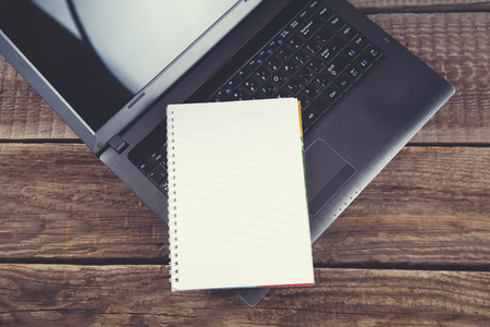 notepad on computer keyboard on wooden table background