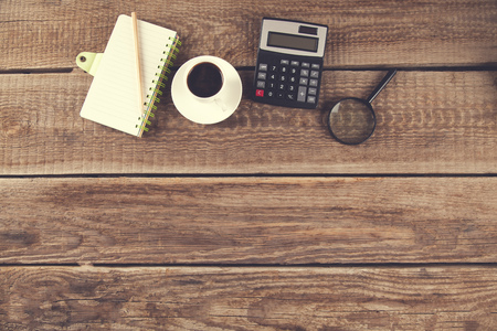 notepad and coffee with calculator and magnifier on desk