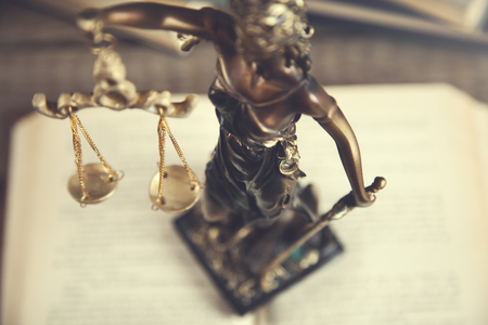 Statue of justice on open book on table