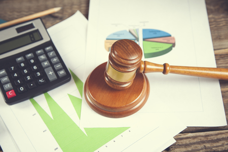wooden gavel and calculator on graph on table