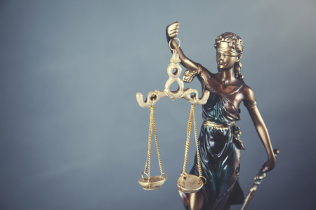 Dame Gerechtigkeit auf Tisch auf grauem Wandhintergrund