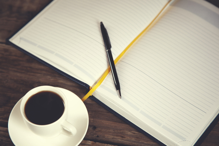 pen on notepad and coffee on wooden desk