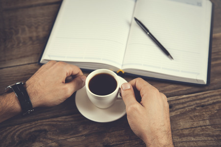man hand pen with notepad and coffee on table