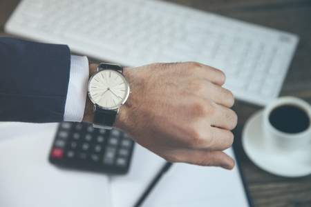 young man hand watch on working table