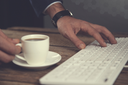 man hand cup of coffee with keyboard on table