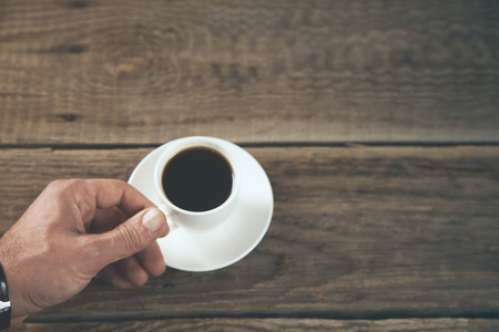 man hand cup of coffee on wooden table background