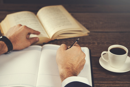 man hand notepad with book and coffee on table