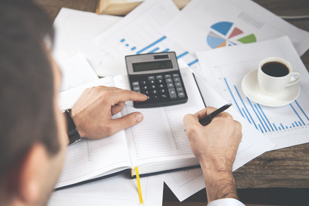 man hand notepad with calculator on graph Reklamní fotografie