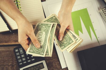 woman hand notepad and calculator with money on table