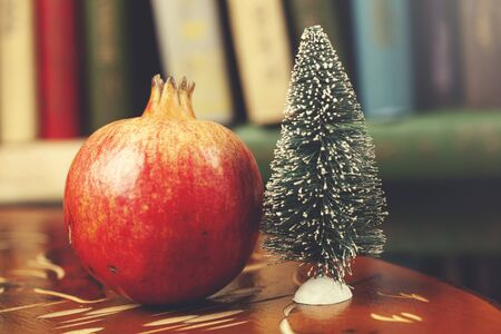 pomegranate with christmas tree on the wooden table