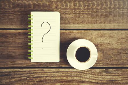 question mark on notepad with coffee on table Imagens