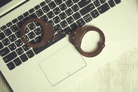 handcuffs on computer keyboard on the table