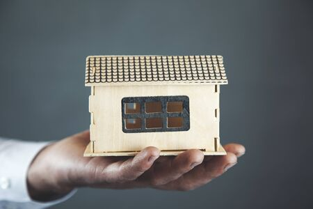 man hand house model on dark background