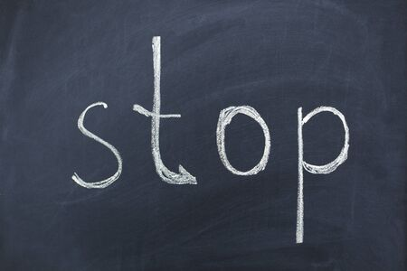 stop text on black chalk board background