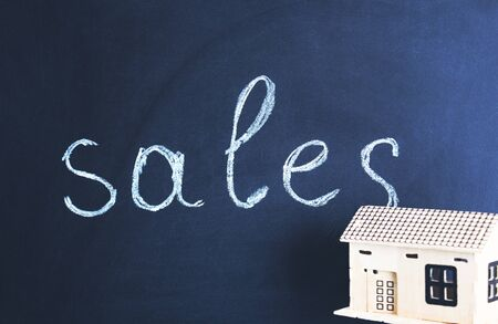 sales text on chalkboard with house model